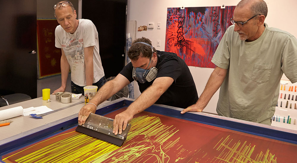 Artist Christian Marclay (left) with Graphicstudio printer Matthew Squires (center) and Studio Manager Tom Pruitt (right). Photo by Will Lytch.